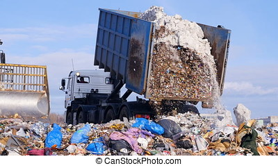 Garbage truck disposed trash on the landfill. Vehicle...