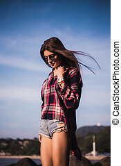 young stylish happy hipster woman traveling around the world wearing aviator sunglasses, denim shirt, tropical island lagoon vacation