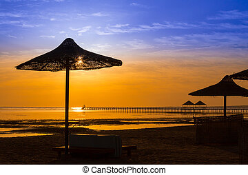 Sunrise at the sea with silhouette of beach umbrellas