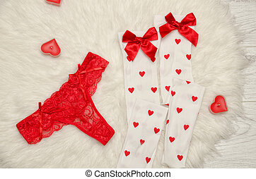 Fashion concept. Red thong panties and white stockings with...