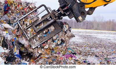 Garbage collecting machine disposed trash on the landfill....