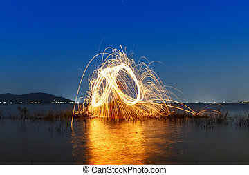 Colorful ring of fire at the lake,Burning Steel Wool...