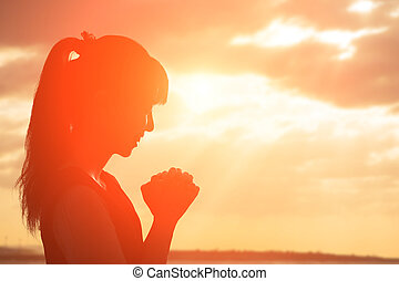 woman pray pious - young woman pray pious with sunrise,...