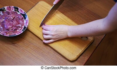 Woman Chef Slices Chicken Liver Meat on a Wooden Kitchen...