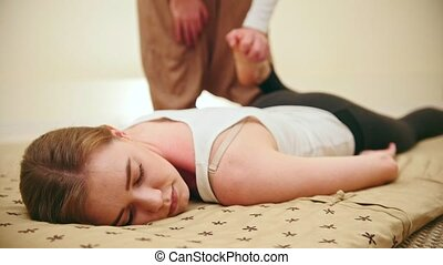 Male masseur holds the thai massage session - stretching of...