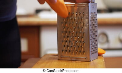 Woman Hands Rubbing Carrots on Grater in a Home Kitchen -...