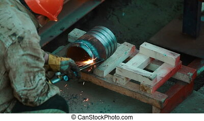 Industrial worker welding metal blank - Worker welding a...