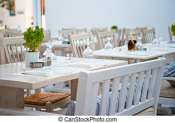 Summer empty openair cafe at greek city - White tables with...