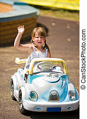 Little driver - Happy little girl riding toy car in lunapark...