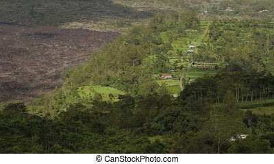 Foot of the Batur volcano. Aerial view from Kintamani. Lava landscape view with forest in cloudy day of winter rainy season. Bali Indonesia