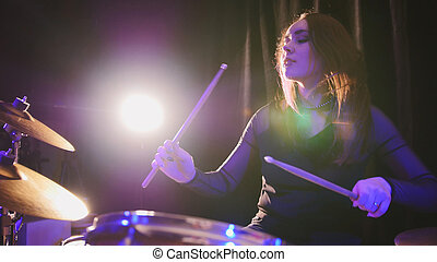 Rock band rehearsing in the garage - attractive girl percussion drummer perform music break down