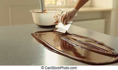 Melted Dark Chocolate mixing on a table