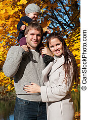 Young family relaxing outdoors In autumn park