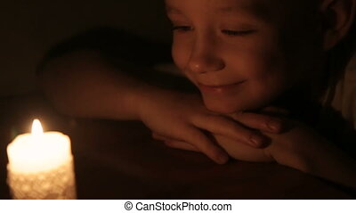 A cute smiling boy looking at a burning candle