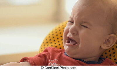 Little baby cries sitting on a chair - toddler threw a...