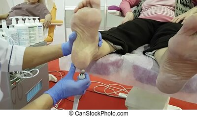 Pedicure specialist works with the patient in clinic