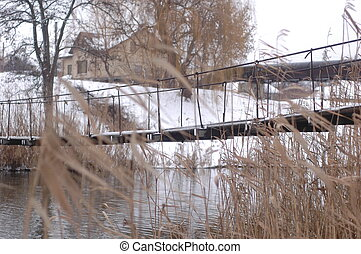 Suspension bridge over a small river against the background...