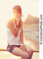Beautiful young blonde woman sitting on the beach. Wearing white T-shirt. Wind is blowing into her long blonde hair. In the background is sunset and warm feeling