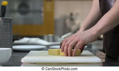 Man hand grating yellow cheese with a metal grater.