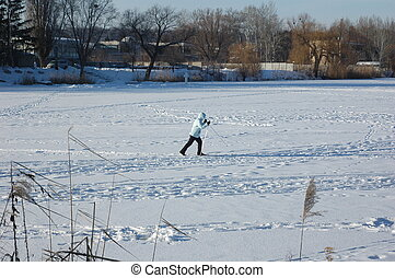girl is skiing on a frozen river.