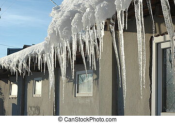 Icicles hang from the roof on a sunny, frosty winter day.