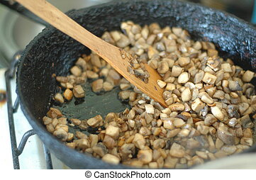Finely chopped mushrooms are fried in an old skillet.