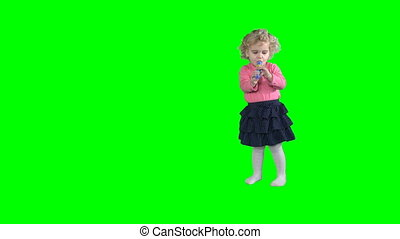 Cute girl child playing with fife pipe and turn around isolated on green