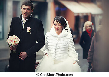 Bride and groom in winter coats walk along the old street