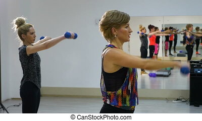Young women doing biceps training with weights at the gym