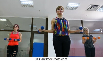 Group of women sweating while working out with dumbbells in...