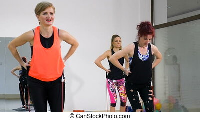 Beautiful active women engaged in weight loss fitness exercise indoor