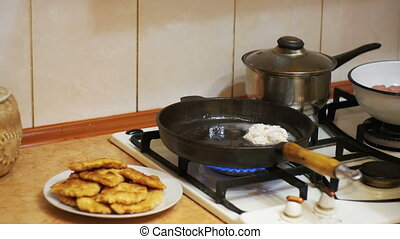 Frying Meat Chops on a Frying Pan in the Home Kitchen....