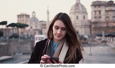 Brunette woman walking in city centre and using smartphone....