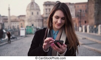 Young happy woman walking in city and using smartphone. Girl...