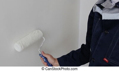 man decorating room - painting wall with paint roller.