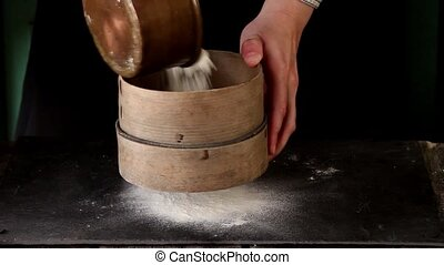 Female hands sifting flour from old sieve on black kitchen...