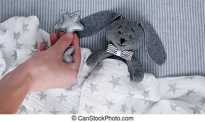mother arranges the stars a child's toy rabbit in a crib