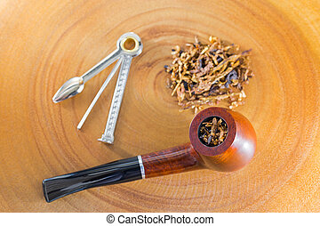 Classic blended aromatic pipe tobacco next to tool to pick...