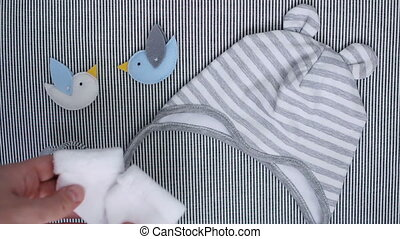 mother puts baby socks on the bed with baby clothes