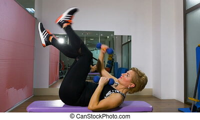 Middle age woman exercising with light weight dumbbells in...