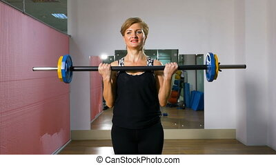 Female bodybuilder exercising with barbell at the gym