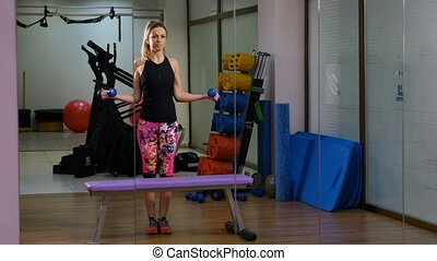 Woman standing in front of mirror making exercise at the fitness gym