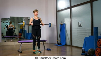Woman holding barbell and lifting it at wellness club