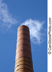 Smoke Stack - A tall brick factory smoke stack billowing...