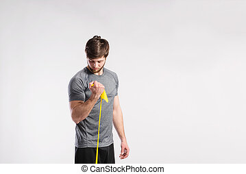 Handsome fitness man working out with rubber band, studio...