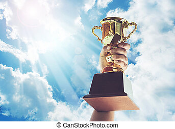 Man holding up a gold trophy cup,win concept. - Win...