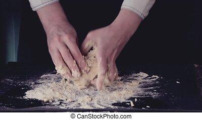 Female hands making dough for pasta over black table. Dark...