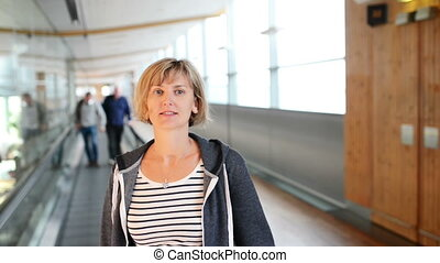 Woman standing on moving walkway in airport - Woman standing...