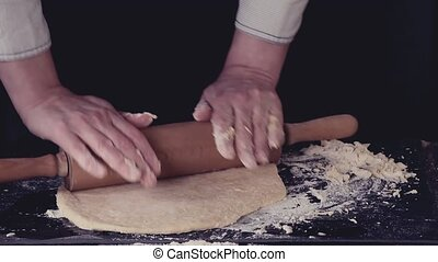 Female hands making dough for pasta over black table. Dark rustic style. In retro filter effect