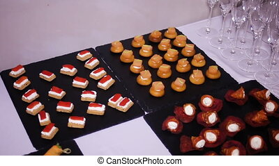 colorful canapes are on the black tray on the table holiday...